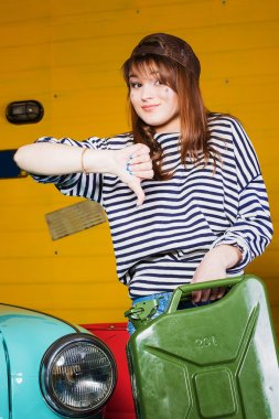 brunette woman in a cap and a striped sweater showing thumbs down and holding an empty canister in the garage