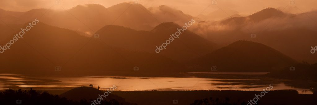 Silhouette of Mountains Above the Water under orange cloudscape clouds at sunset