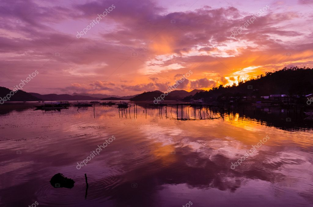 Pretty Pink orange Sky cloudscape over an island with reflection at Sunset on the Island of Coron