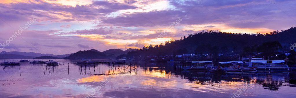 Pretty Pink orange Sky cloudscape over an island with reflection and wooden traditional filipino boats at Sunset on the Island of Coron