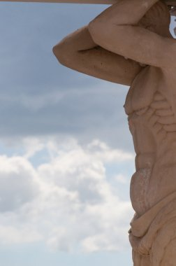 Close-up of Muscular stone Sculpture in front ol a cloudscape