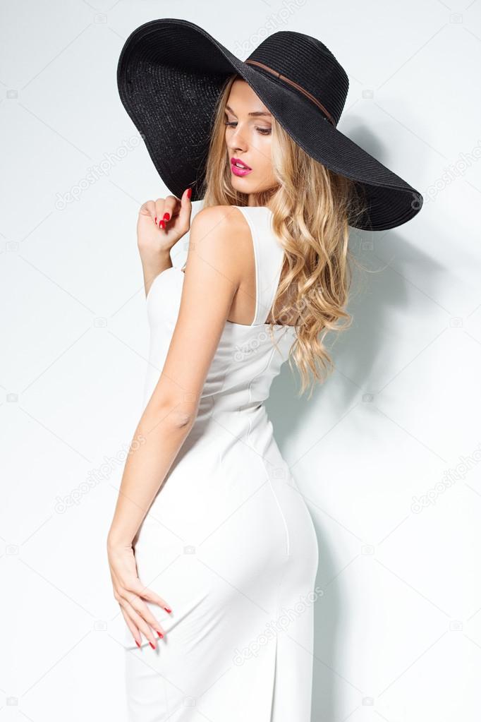de40a751f5cb Bella donna bionda in cappello nero e bianco elegante abito da sera in posa  su priorità bassa isolata. Look alla moda — Foto di ...