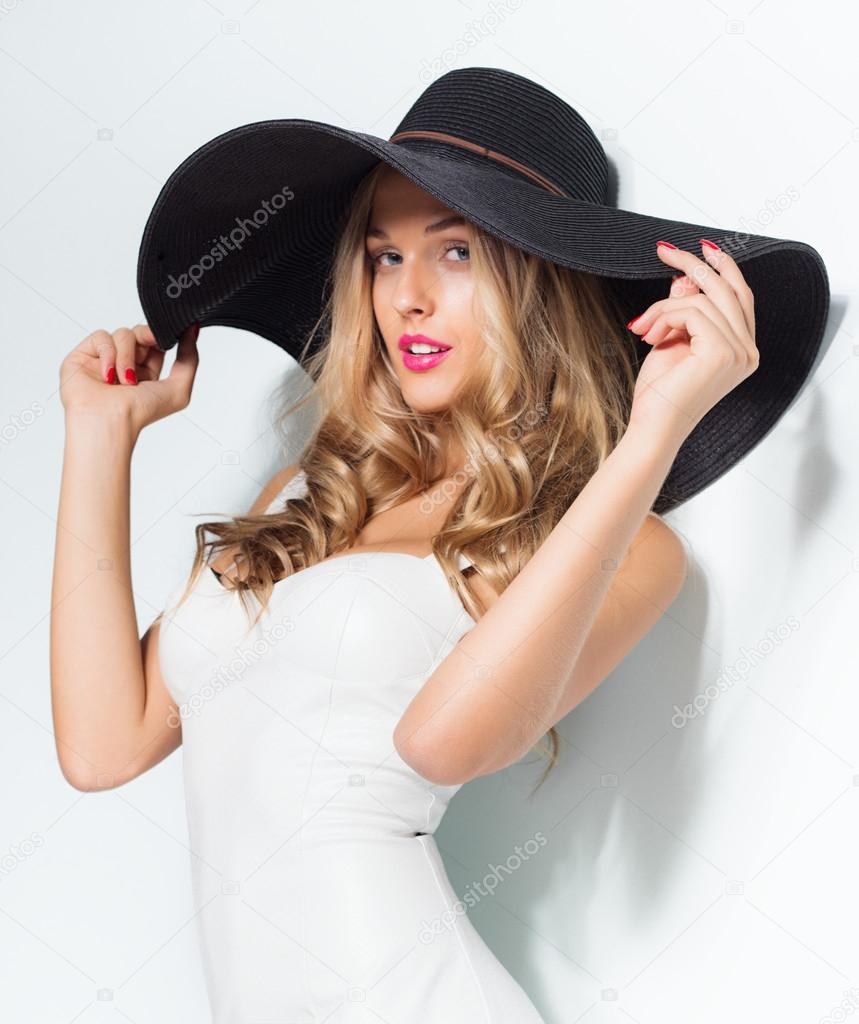 Beautiful blonde woman in black hat and white elegant evening dress posing  on isolated background.Fashion look — Photo by wehands 323968466f0