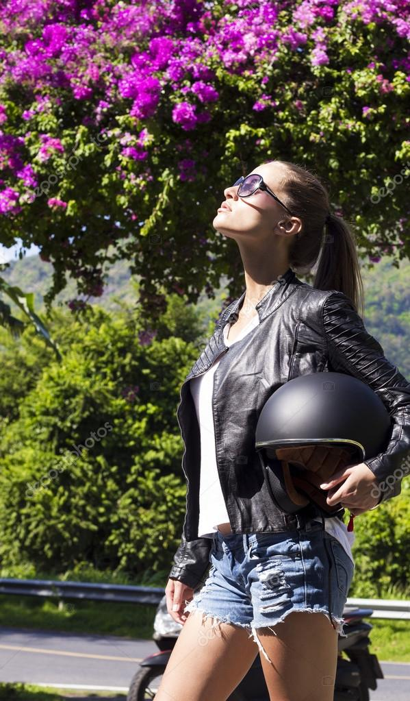 Beautiful fashion woman in black leather jacket with helmet on road. Phuket island, Thailand