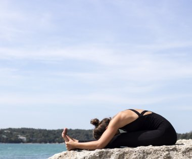 Yoga woman poses on beach near sea and rocks. Phuket island, Thailand