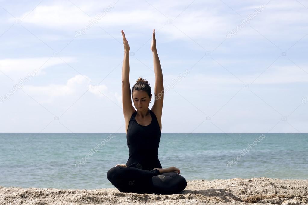 Yoga woman poses on beach near sea and rocks. Phuket island, Thailand