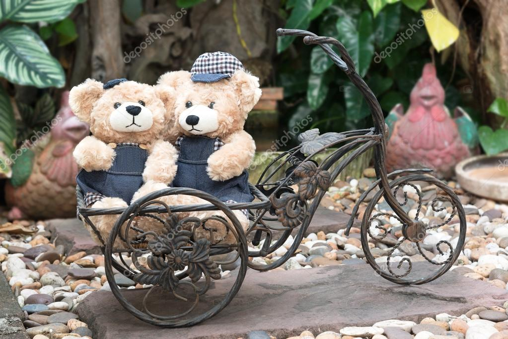 two teddy bears on garden background