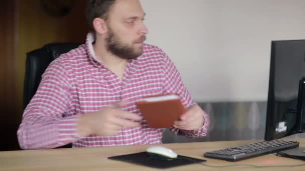 man checked with a diary at the computer