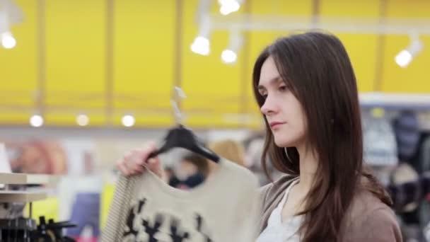 mladá žena si vybírá oblečení v obchodě