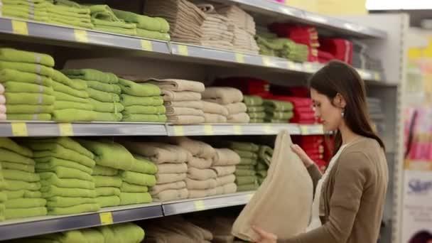Mladá žena si vybírá ručníky v supermarketu