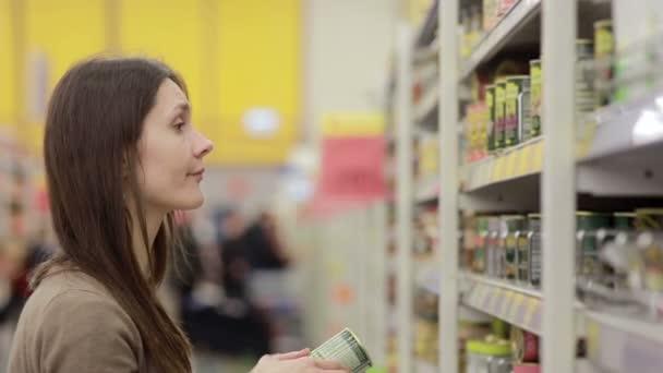 Fiatal nő választja a konzerveket a boltban