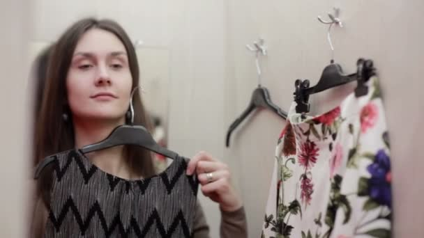 Beautiful girl trying clothes in a fitting room