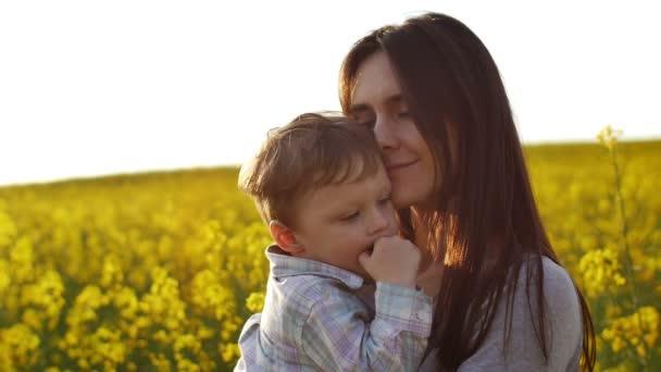 matka drží svého syna na poli při západu slunce. Pomalé mo