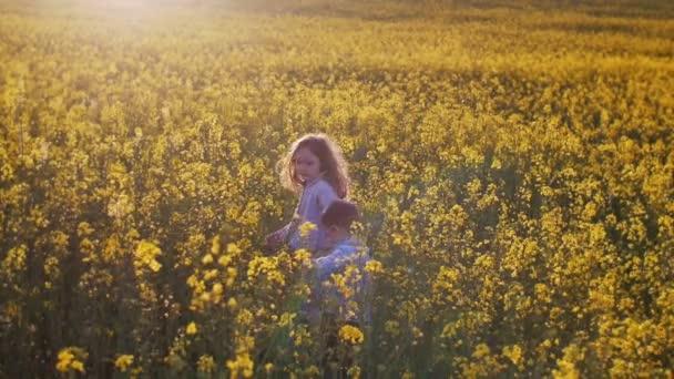 Kis lány és egy fiú egy mezőben a naplemente. Lassú mo