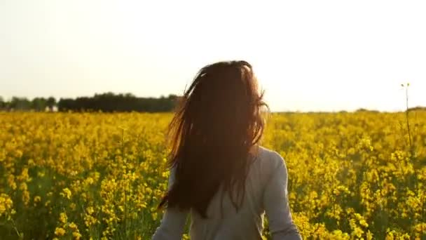 girl runs arms outstretched through a field slowmo