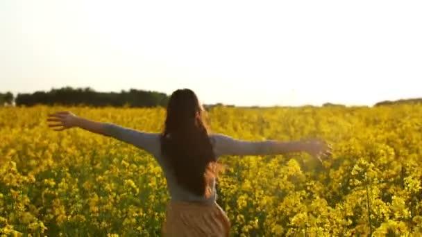 Mädchen läuft mit ausgebreiteten Armen durch ein Feld