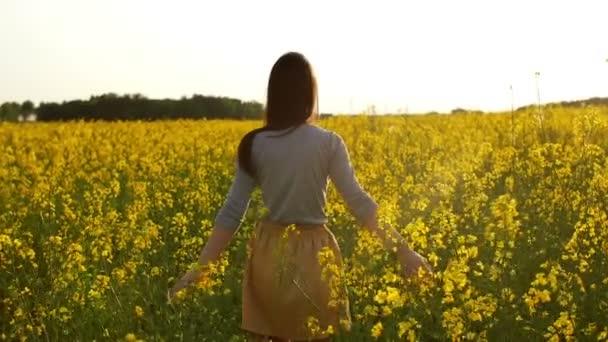 schönes Mädchen geht bei Sonnenuntergang durch Feld