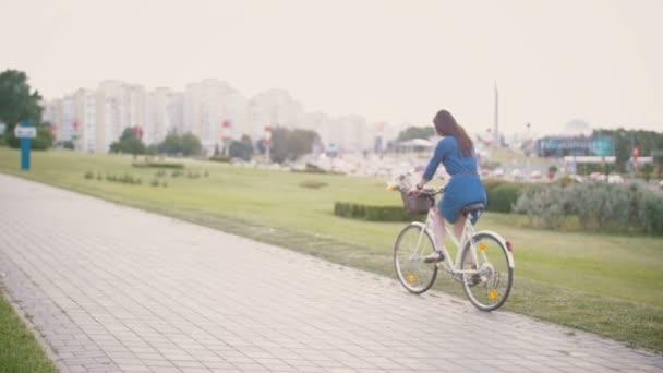 Zadní pohled na dívku, jízda na kole s květinami a francouzský chléb v košíku v městě, pomalé mo, steadicam shot