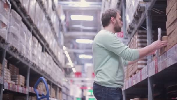 A man is standing near shelves with goods in cardboard boxes and checking his list in a warehouse