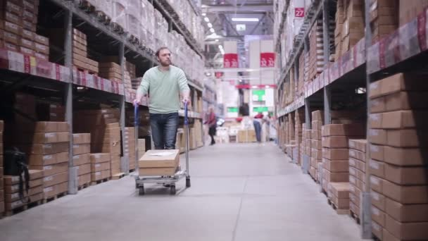 A man pushing a trolley in a warehouse. He is checking his list and taking necessary boxes