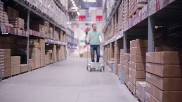 A man pushing a trolley in a storage warehouse is moving into the camera, slowly getting into focus