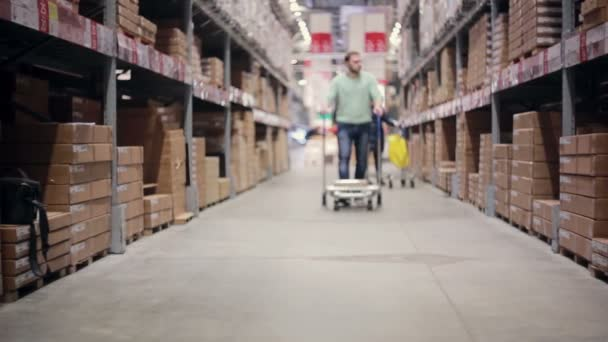 A man pushing a trolley with a box on it in a warehouse is moving into the camera, slowly getting into focus