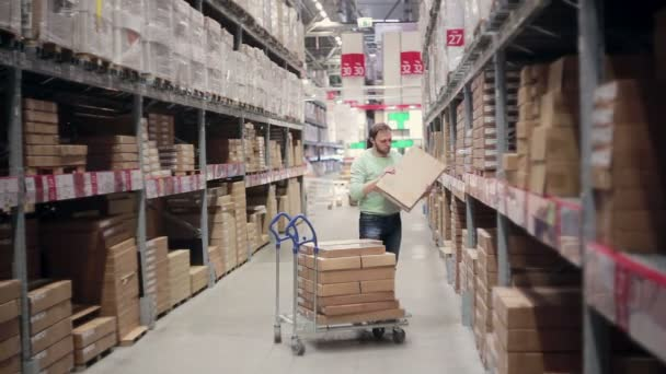 A man is taking a cardboard box, putting in on a trolley and pushing the trolley. Storage warehouse