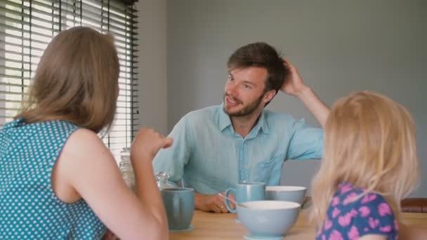 Mladý tmavovlasý otec má rozhovor se svou krásnou ženou u kuchyňského stolu. Zpomaleně