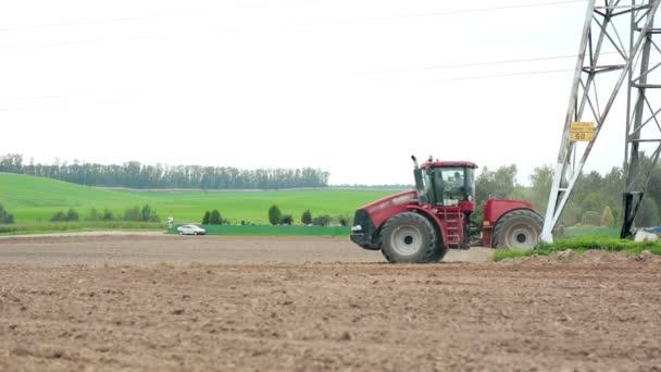 Zemědělský traktor orat pole. Kopce a lesy v pozadí.
