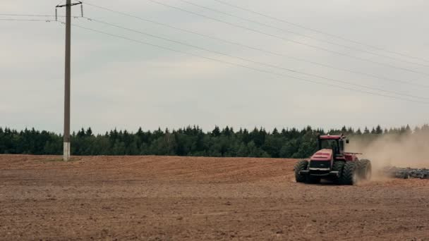 An agricultural tractor plowing a field before sowing, moving to the camera. A forest at the background, soil dust