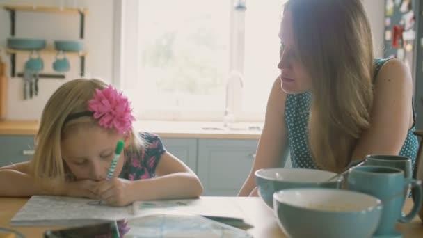 Mutter lächelt während im Gespräch mit ihrer kleinen Tochter, die ...