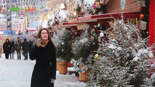 Young beautiful woman is walking and examines souvenirs in snowy weather on the Christmas market in Moscow, Russia