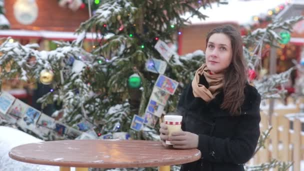 Beautiful young woman drinking hot tea during the Christmas Fair
