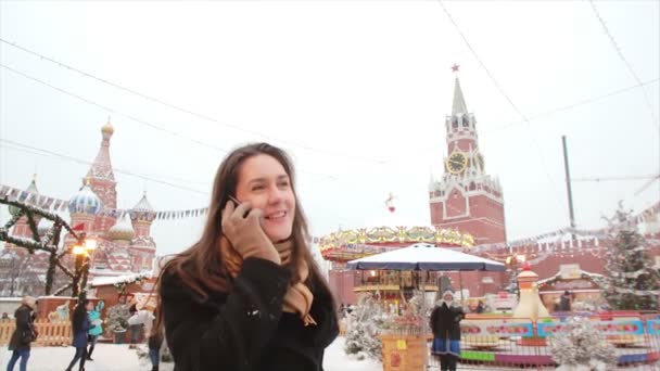 Woman talking on phone standing in the winter on the Red Square in Moscow, in front of Kremlin and St. Basils Cathedral