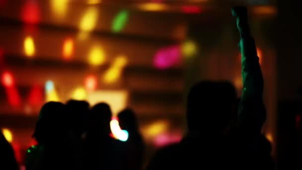 silhouette of a dancing man jumping into a crowd of people on a background of light show