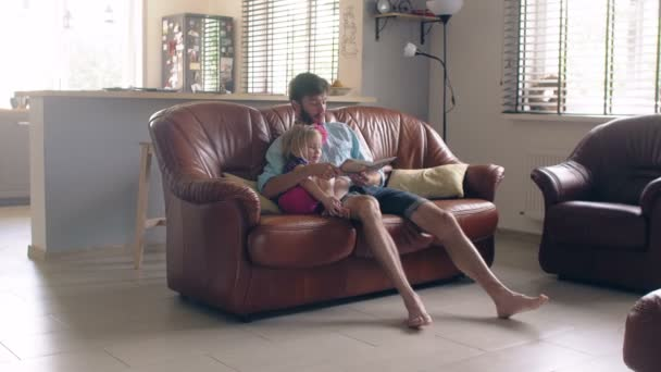 Happy family. young father and his little blond daughter are reading a story on leather sofa in the dining room. 4K