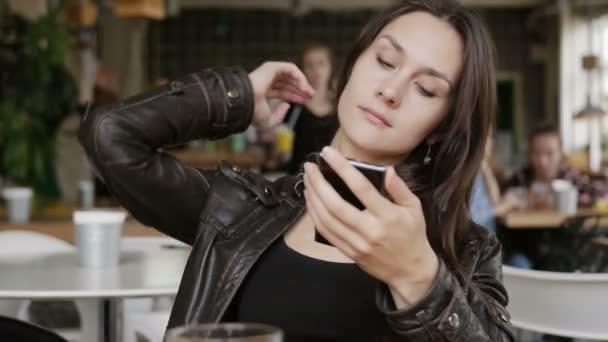 Elegantní mladá žena používá smartphone sedí u stolu v moderní kavárně, narovná vlasy, s úsměvem. 4k