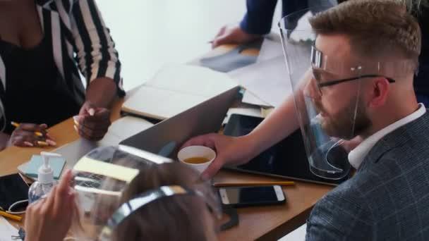 COVID-19 Sicherheit wird zum Lebensstil. Glückliche junge, vielfältige Geschäftsleute beim Brainstorming im modernen Büro unter Gesichtsschutz.