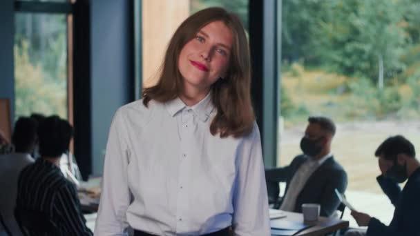 Portrét mladé šťastné atraktivní gen-z brunetka vůdce obchodní žena pózující na kameru na lehkou kancelář zpomalení pohybu.