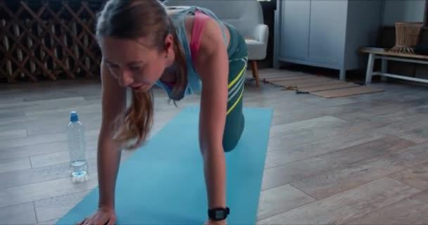 Krásná sportovní odhodlaný mladý kavkazský žena unavený z fitness cvičení doma s chytrými hodinkami na sebe izolace.