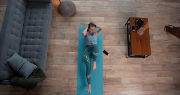 Top pohled krásný sportovní mladá blondýna žena unavená dělá fitness abs cvičení s chytrými hodinkami doma na karanténě.
