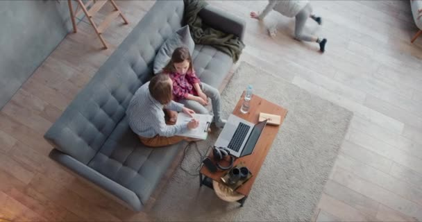 Top view young happy single mother helping teenage son and daughter study at home. Family homeschooling on quarantine.