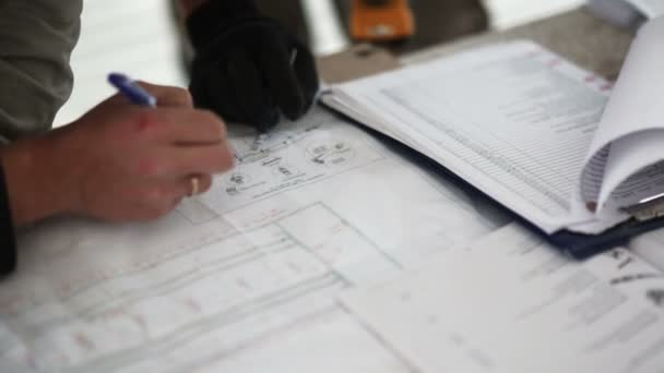 Engineer and worker checking blueprint work. Drawing