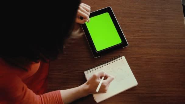 Žena pracuje na tabletu, skici v poznámkovém bloku. zelená obrazovka