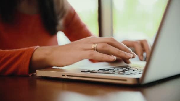 Frau tippt auf Laptop, Computer im Café. statisch