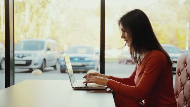nő gépelés-on laptop, mosolyogva kávézóban. Profil