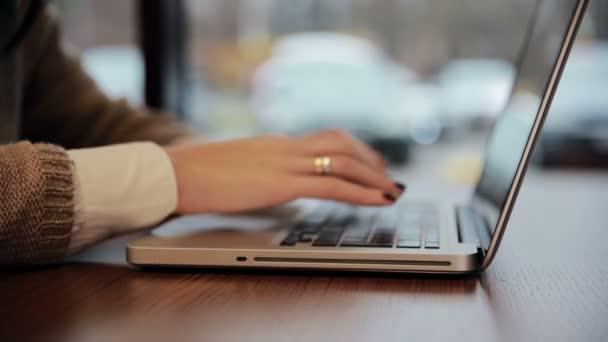 Ženské ruce pracují na notebooku v kavárně. statický
