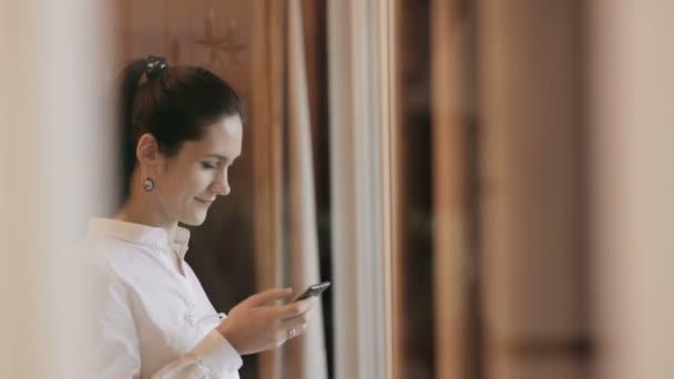 Žena, odesílání zpráv s telefonem u okna