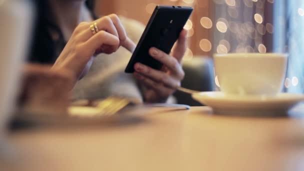 Žena ruce SMS, pomocí smartphone v kavárně.