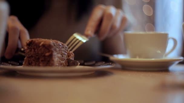 Dívka jí dort a pití kávy v kavárně